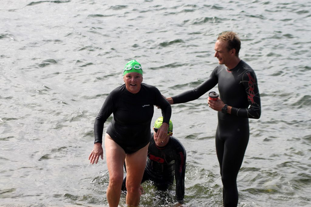 A woman exits the water as another participant greets her