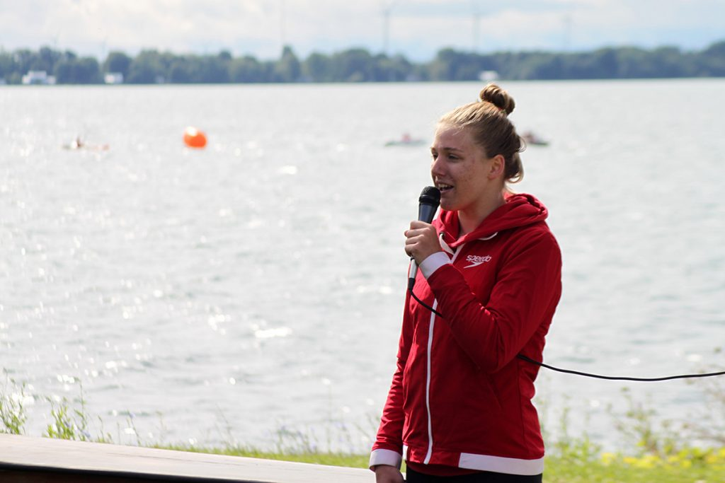 A girl gives a speech into a microphone with the lake behind her
