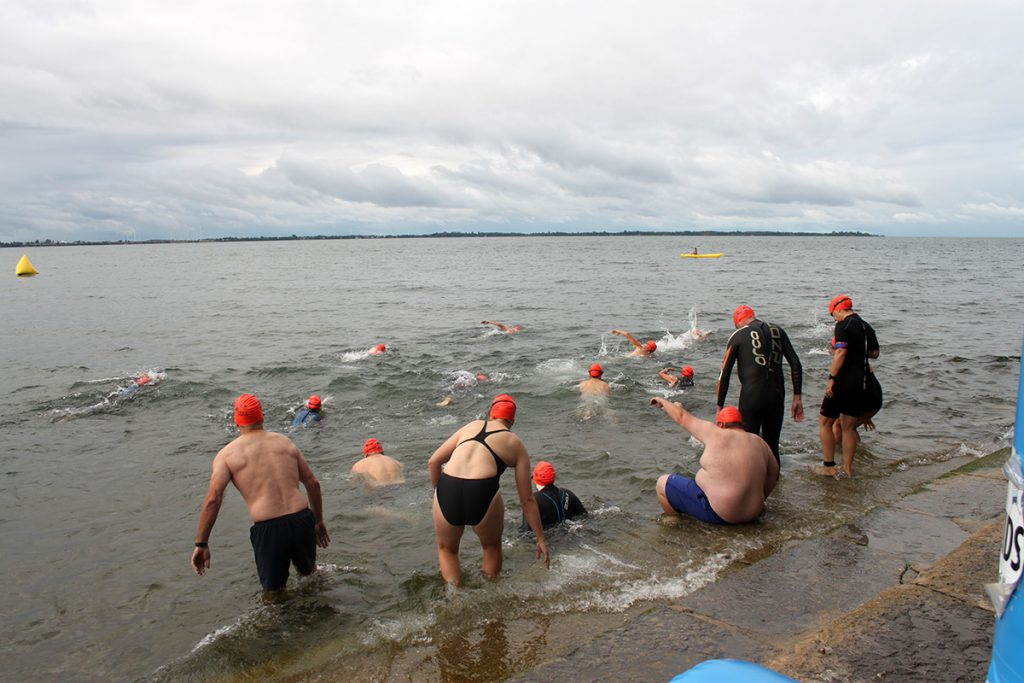 Swimmers enter the water wearing orange caps