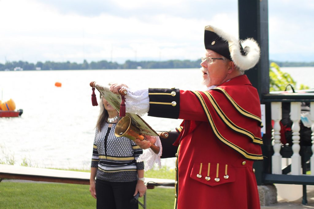 The town crier dressed in a red frock reads from a scroll