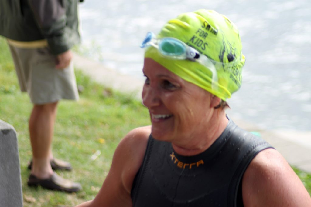 A swimmer smiles wearing a bright yellow cap